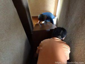 急こう配の階段で荷物をおろしているふたりの男性です。